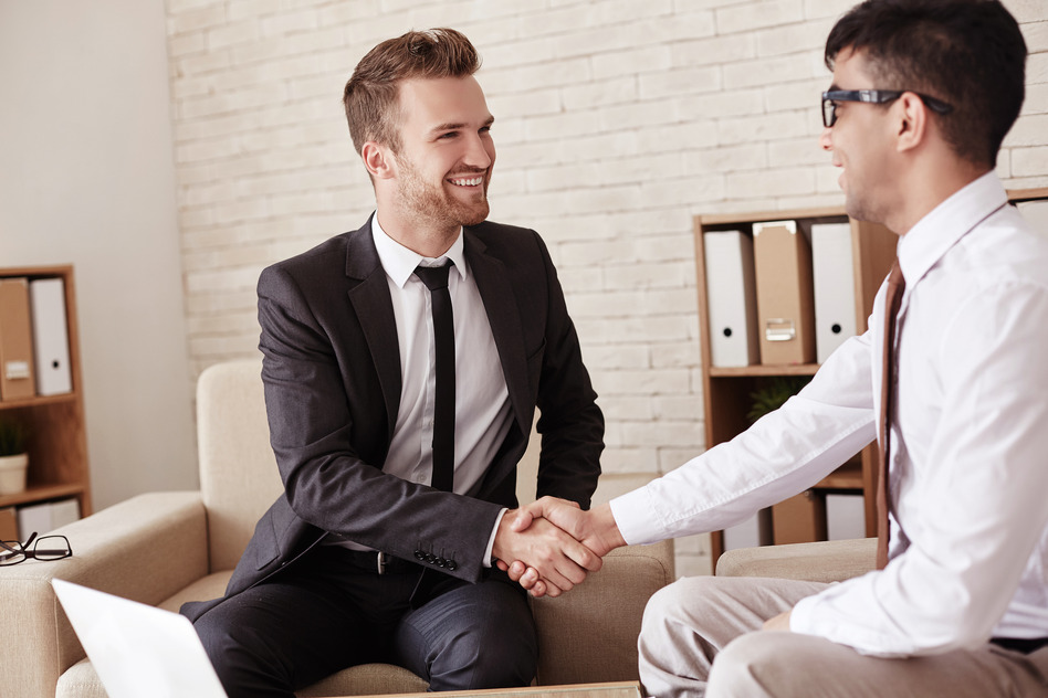 Business partners handshaking in office before meeting